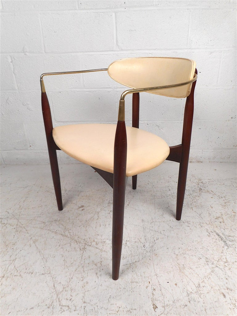 Stylish Mid-Century Modern chair manufactured by Kedawood Furniture. Unusual design with tapered legs, contoured brass armrests, seat and backrest covered in a vintage white vinyl. This chair is sure to make a great addition to any modern interior.