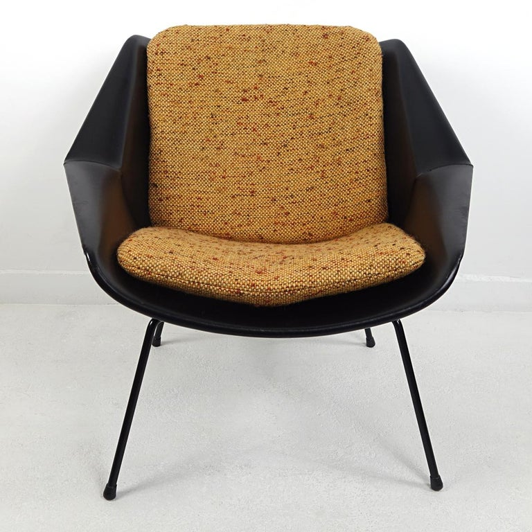 This easy chair was designed by Cees Braakman in the 1950s for famous Dutch furniture manufacturer Pastoe. Its shell is covered in black vinyl, standing on four elegantly shaped black steel legs. The shell holds two loose cushions upholstered with a
