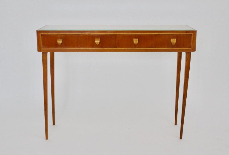 This presented sideboard or commode was made of solid cheery wood, maple tree veneer, plywood, fibre board and brass details. Designed and executed in Italy in the 1950s.  The elegant sideboard shows four drawers with curved wooden draw-handles. At