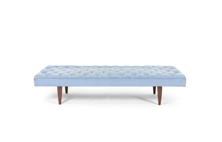 Chesterfield tufted daybed bench. Designed by Kipp Stewart for Calvin Furniture. Original tufted blue leather has great broken-in patina. Walnut legs have been refinished, cushion support strapping replace.