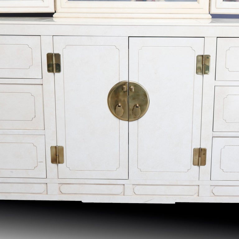 A Mid-Century Modern dresser by Hickory white offers Chinese Chippendale styling with all-over ivory enameled finish, pierced corbels having Asian influence, and cast brass hardware and accoutrements. Case with adjustable triptych mirror surmounting