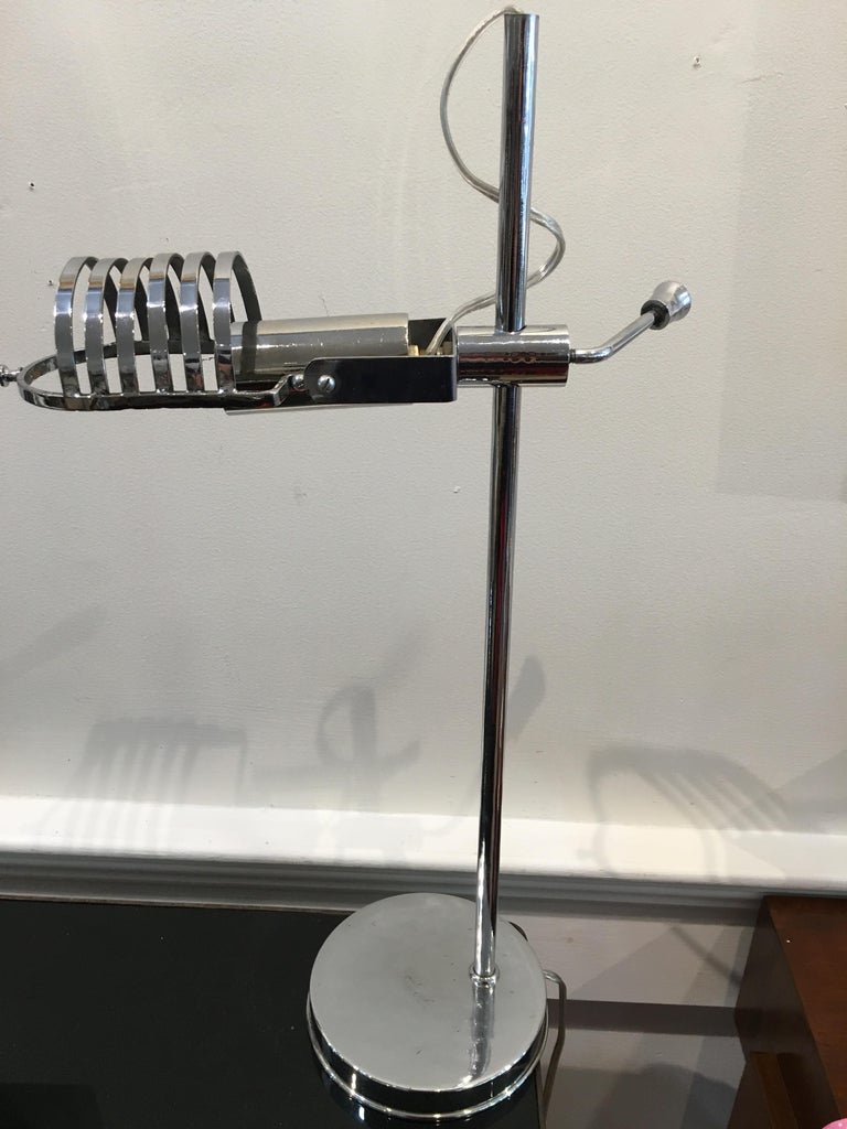 Mid-Century Modern chrome desk light. It adjusts up and down using the lever and the open work shade portion tilts up and down. It takes a European base bulb, which are easy to find. Rewired for American use. Very sculptural yet practical. Base