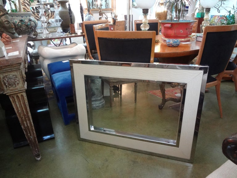 Stunning Mid-Century Modern Milo Baughman style chrome and faux alligator mirror. This beautiful mirror has a double chrome frame inset with cream colored faux alligator. Our versatile well made midcentury mirror is finished on the back with