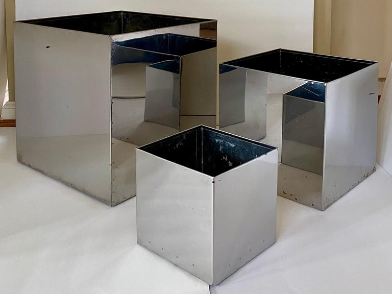 Minimalist Mid-Century Modern group of three shiny mirror finish chrome steel planters in various sizes. These cachepot vessels can be used to house your potted plants or used as multi-purpose containers. Sculptural and geometric pieces have a