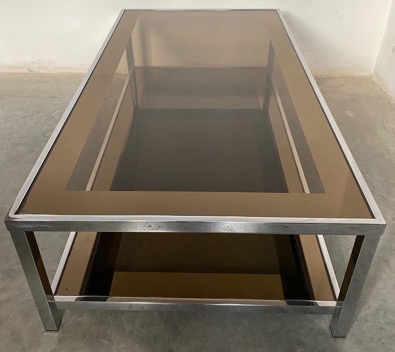 Belgo Chrome was well known for its handsome clean designs in metals and mirror. This 1980s coffee table is iconic of their designs. The 2 smoked glass tops are smoked glass and have a mirrored bronze border 7 cm wide. The border further emphasizes