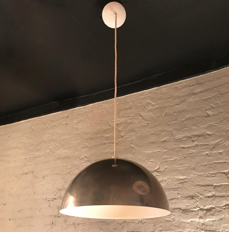 Mid-Century Modern pendant light features a wide dome shade with chrome exterior and newly painted white interior with white canopy. The lamp is wired to accept up to a 200 watt bulb and has an overall height of 45 inches.