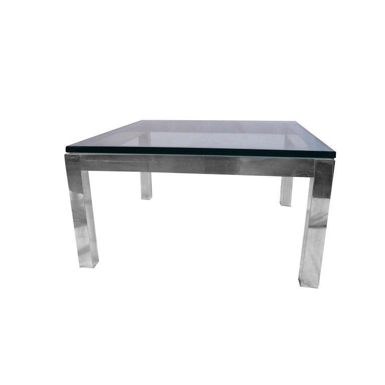 A stylish, bold, low square, polished chrome, and glass coffee table, Milo Baughman style. Features 2? thick chrome frame, supporting a large 1? thick glass top, square legs complement the overall shape of the base, giving it an air of solidity.