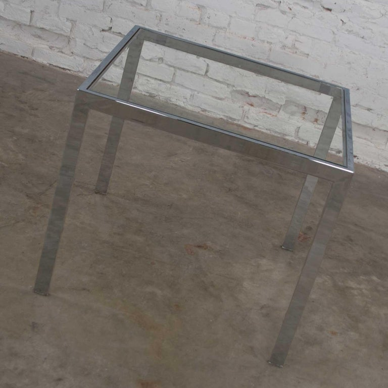 Handsome Mid-Century Modern chrome and glass square Parsons style end table or side table after similar designs of Milo Baughman. It is in wonderful vintage condition. The chrome tube frame does not show any outstanding flaws but there is a bit of