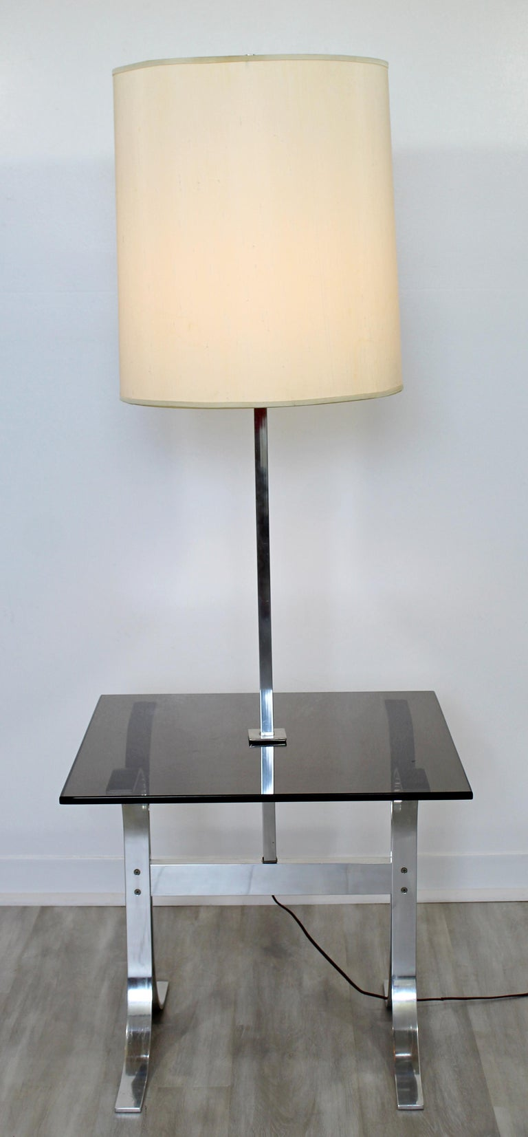 For your consideration is a gorgeous, chrome floor lamp, with a smoked glass table attached, circa 1970s. Includes original shade and finial. In very good vintage condition. The dimensions are 22