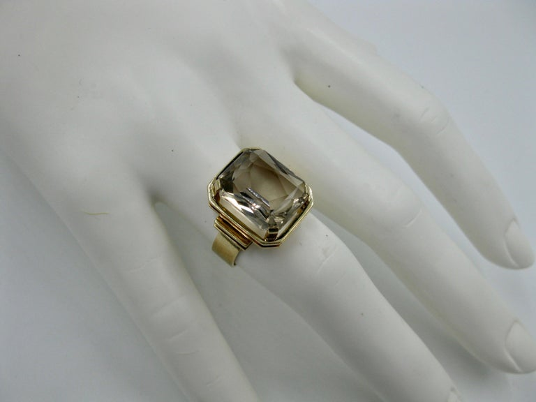 The stunning emerald cut Citrine 14 Karat Gold mid-century modern ring was made in Finland in 1960. A ring created by the esteemed Finnish Jewelry designers from the Mid Century Modern period in Scandinavia. The beautiful Citrine is emerald cut and