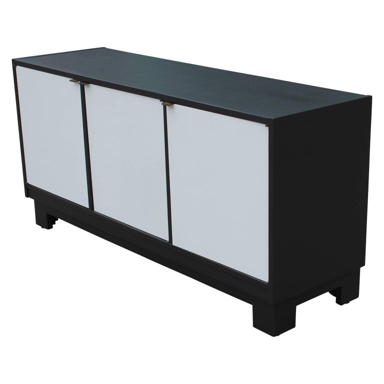 Modern Minimalist charcoal and grey credenza with brass hardware. The two left doors open to reveal single drawers with ample cabinet space below. The door on the right opens to show a single shelf.