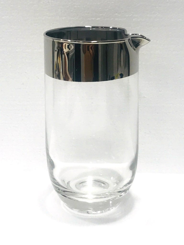 Mid-Century Modern cocktail shaker or carafe by Dorothy Thorpe, known for her iconic barware designs, circa 1960. The glass cocktail mixer has a minimalist design featuring a striking silver overlay rim and a tapered base.