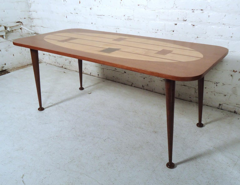Vintage modern coffee table featuring a modern inlay design top, rich walnut grain, and tapered legs.  Please confirm item location (NY or NJ).