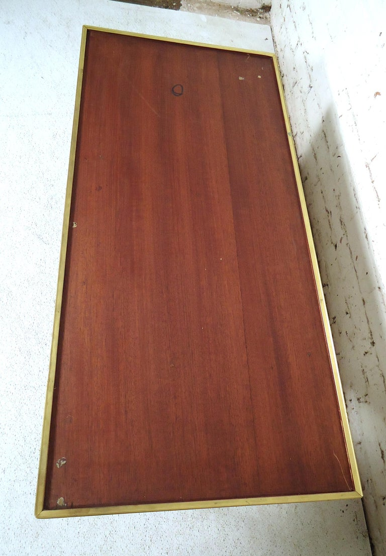 Vintage modern coffee table featuring rich walnut grain, brass frame and legs.  Please confirm item location (NY or NJ.)