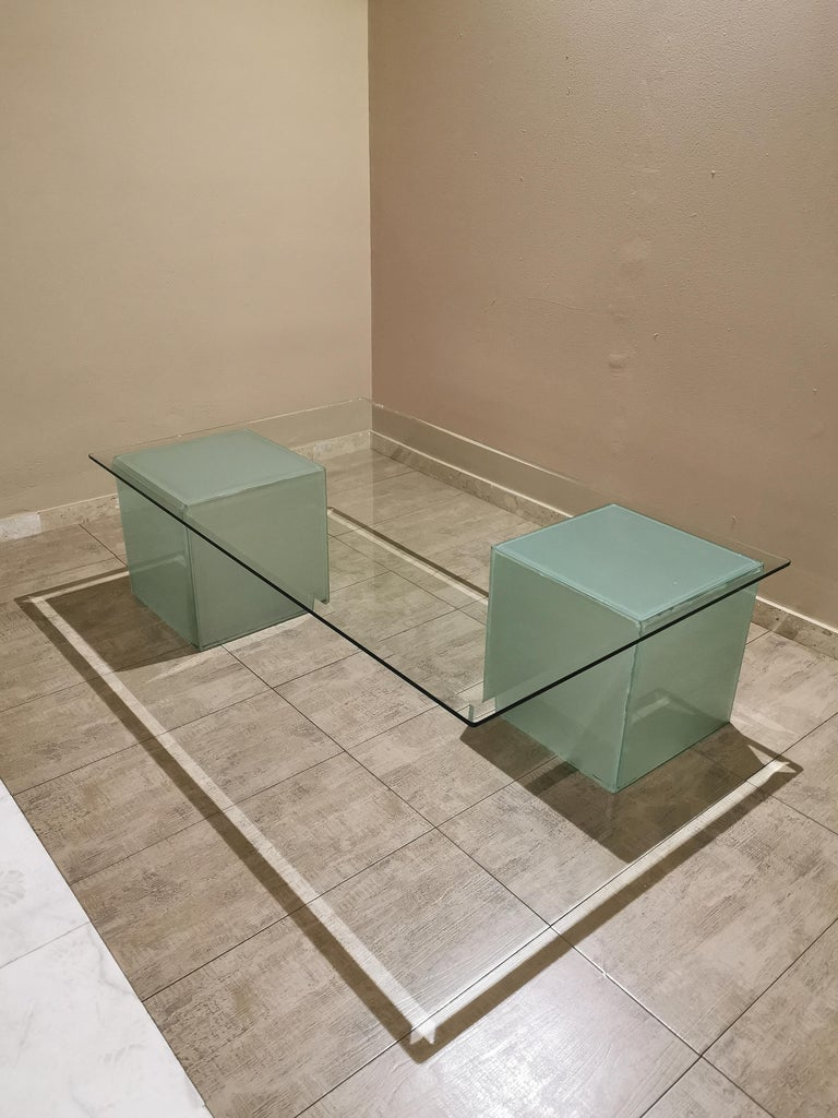 Large coffee table with rectangular cut transparent glass top that rests on 2 cubes of a particular frosted glass that gives water green reflections. The characteristic of this piece are the 2 cubes that can be arranged to your taste being