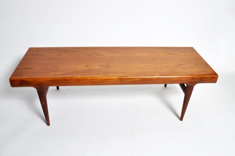This sleek and very simple Danish, modern, table has a solid teak frame and teak veneer top. The solid hardwood legs are elegantly tapered. One end features a drawer and the other end features a pull-out surface extension.