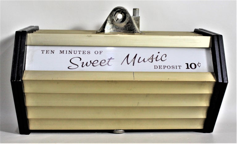 This coin operated commercial music box has no label or maker's mark on it, but it is presumed to have been made in the United States in approximately 1965 in the period Mid-Century Modern style. This wall mounted music box is done with gold tone