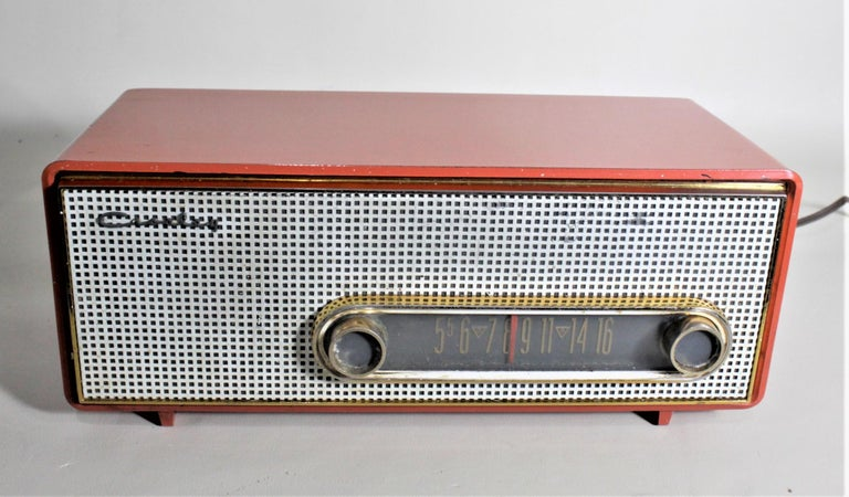This Mid-Century Modern working tube radio was made by Crosley in Toronto Canada in approximately 1965 in the period stream-lined style. The radio is done with a molded coral pink plastic case with a white grill and gold toned details to the dial