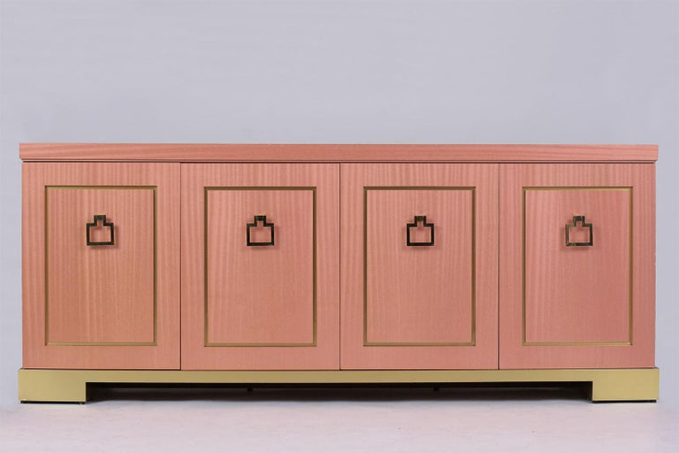 This Mid-Century Modern credenza is in great condition, made out of wood veneered with laminated in a unique pink color. The piece comes with four doors with large eye-catching brass drop handles, has a large single shelf for additional storage