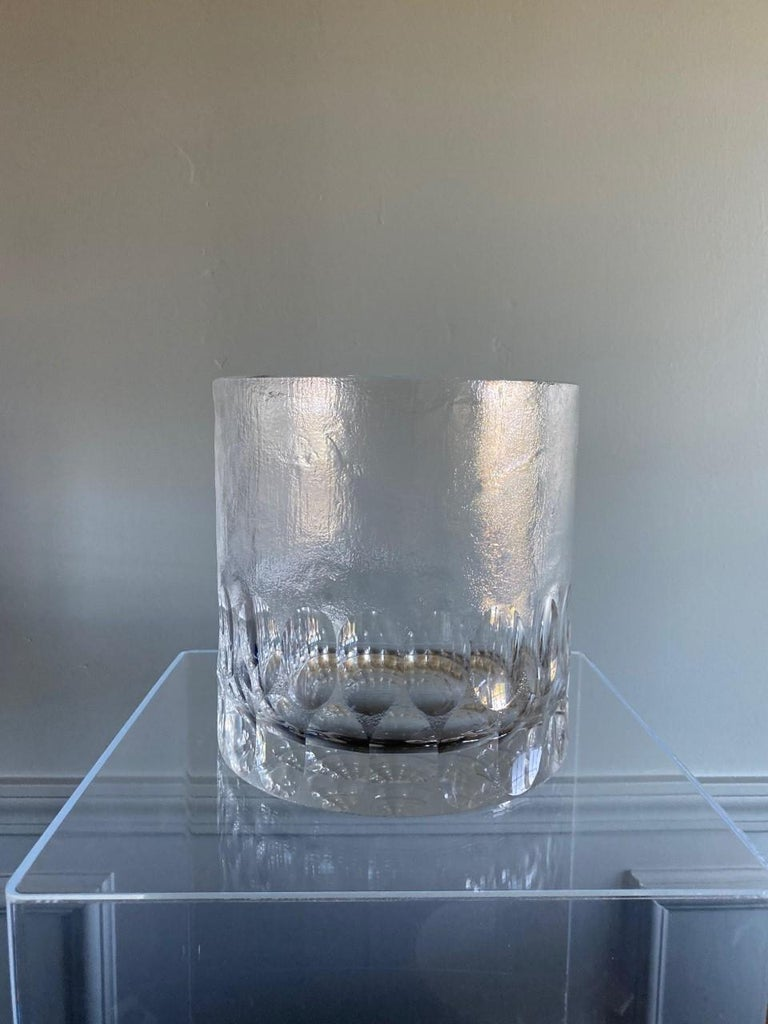 Beautiful and chic Mid-Century Modern crystal ice bucket. This beautiful piece features heavyweight handcrafted crystal with scalloped fluted edges on and above the base. A frosting glass treatment to mimic a frothy sea foam effect envelops the