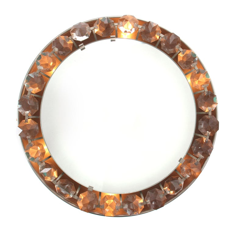 A Mid-Century Modern wall mount mirror framed by a row of large back lit crystals. Made in the USA, circa 1950s.