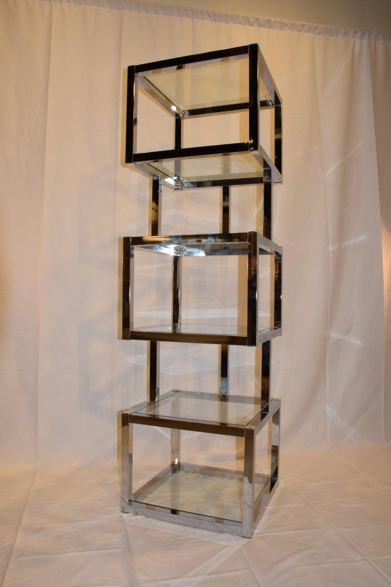 This is a Mid-Century Modern cube chrome and glass étagère. The étagère features cube shaped display units with six glass shelves which includes glass on the top. This is a wonderful piece to display your treasures or books adding sleek modern