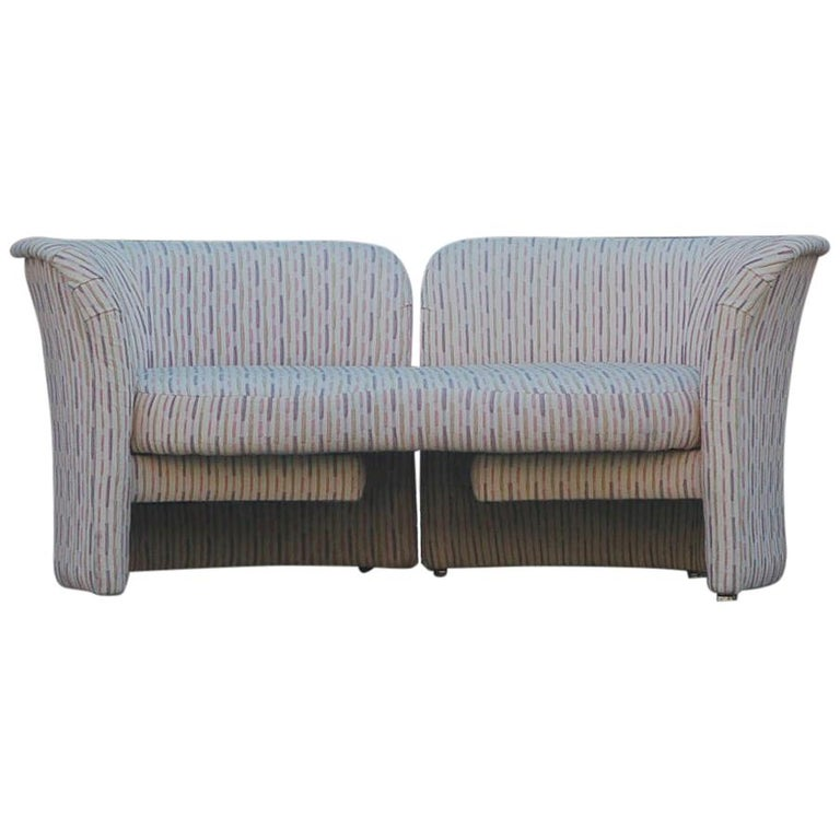 An innovative loveseat designed by Randy Culler and produced by Thayer Coggin in the 1970s. This sofa has a rotating arm on one side to make a chaise lounge or a tete a tete. Sofa retains its original fabric. Its clean but dated. Manufacturers label.