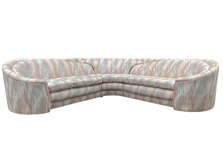A curvy three piece sectional designed by Carson's Furniture and produced in the early 1980s. It features a unique over lapping cushion design. Fabric is original, and dated, but usable if desired. Manufacture labels.