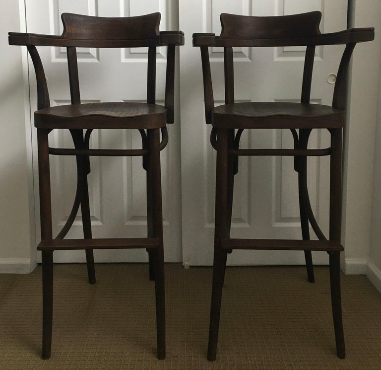 Set of two rare Czechoslovakian Mid-Century Modern Bentwood tall barstools. Sleek and sculptural bentwood Thonet style wood frames with original dark walnut finish patina. Features comfortable hand carved seats and arm rests. 