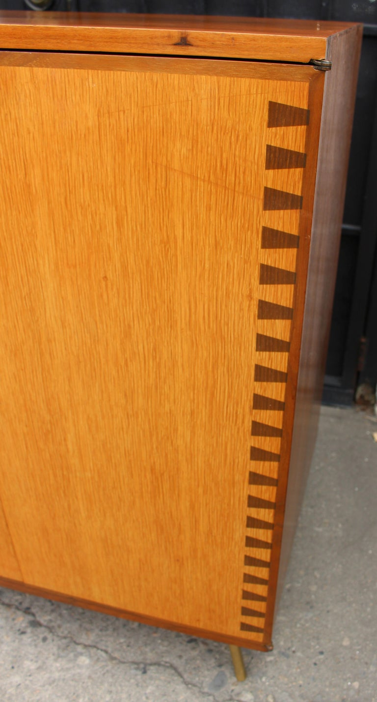Teak Danish 1960s cabinet. Brass legs and the solid inlaid wood  on the side of the cabinet.