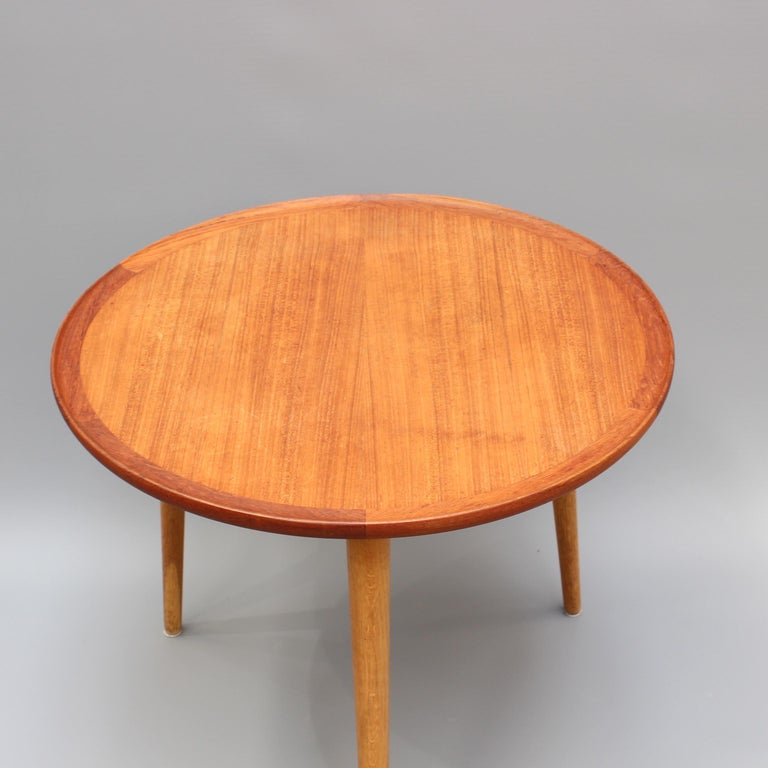 Mid-Century Modern Danish circular teak end table, circa 1960s. A sturdy, mid-weight, three-legged end table which is sure to be a conversation piece in any room in which it is placed. Commensurate with its age, there are characterful markings on