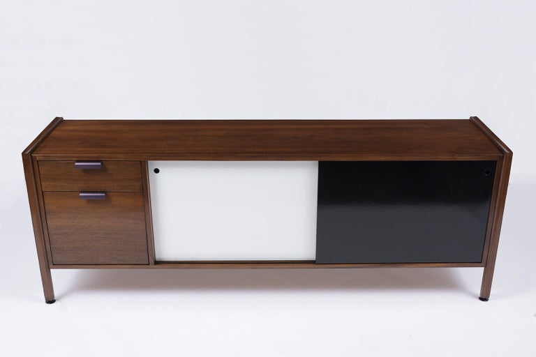 This Mid-Century Modern Sideboard is made out of walnut wood, fully restored, and has been newly finished in a walnut color stain with a white and black multi-color combination with a newly lacquered finish. The Credenza also features two pullout