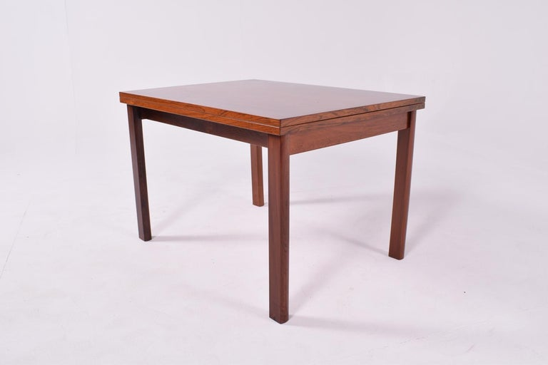 A spectacular flip top coffee table. With a solid rosewood frame and rosewood veneers on the top. The top swivels and opens on two solid brass hinges. Transforming the size to 126 long by 86 wide. Excellent and elegant rosewood veneers, very