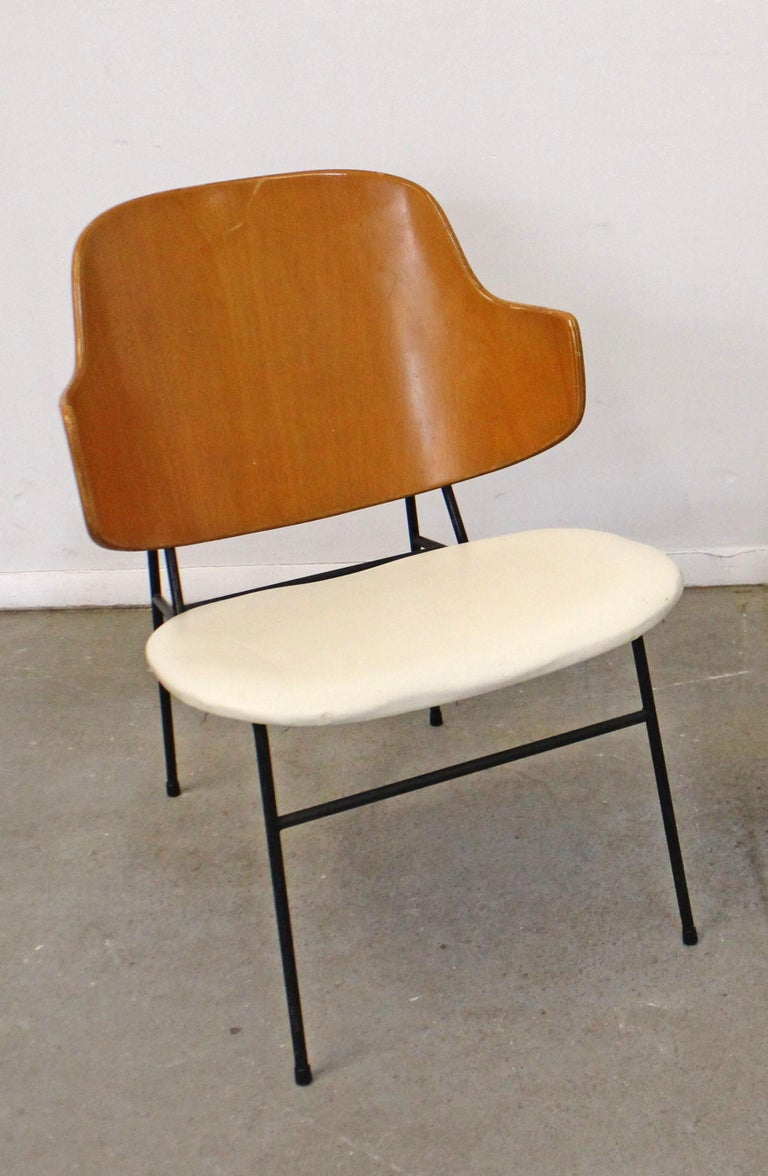 What a find. Offered is an original 'Penguin' chair designed by IB Kofod Larsen for Selig. This chair was designed in 1953 and had a limited production through the 1960s. This chair has a metal base, wood back, and vinyl seat. In good, structurally