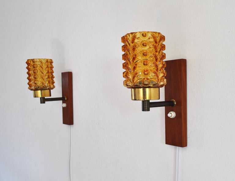 Mid-Century Modern pair of wall lights in solid teak, brass and amber colored glass shade, Denmark the 1950s. Very good vintage condition.  Dimensions: Height: 20 cm Width: 7.5 cm Depth: 12.5 cm Glass shade: diameter 7.5 cm, height (visible