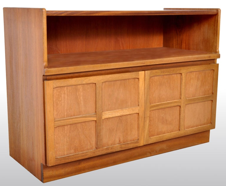 Mid-Century Modern Danish style media cabinet in Teak by Nathan Furniture, 1960s. The cabinet having a recessed cavity above twin paneled cupboard doors and standing on a plinth base. The cabinet bearing the original