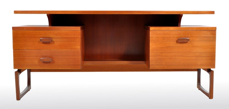 Mid-Century Modern Danish style teak floating top desk by Ib Kofod-Larsen for G Plan, 1960s. The desk having a curvilinear floating top writing surface above twin pedestals, to the left a bank of two drawers and to the right a single cupboard. The