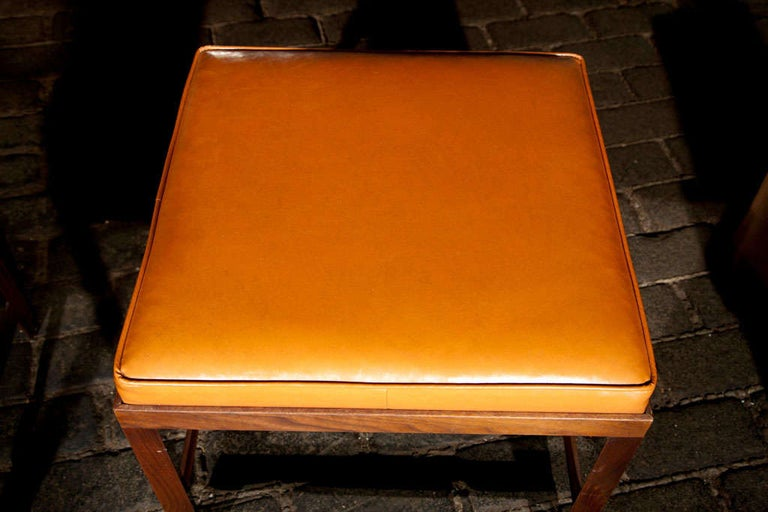 Simple rectilinear shaped bench with original orange vinyl cushion from the 1960s.