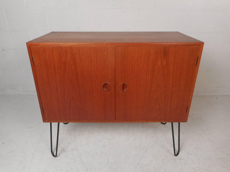 This stunning vintage modern case piece features two cabinet doors with half moon recessed pulls hiding two large compartments with shelves. This Danish modern cabinet sits on top of sturdy black metal hairpin legs. An elegant teak finish