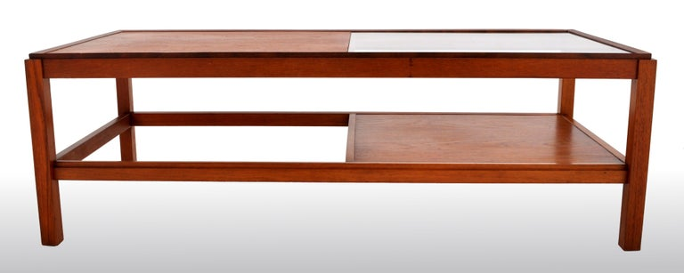 Mid-Century Modern Danish teak coffee table, 1960s. The twin-tiered table of large form having a glass inset to the top and having a secondary tier underneath. The table made of solid figured teak and raised on square legs.