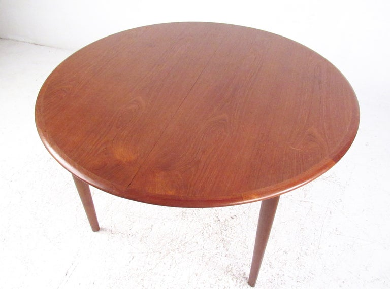This beautiful vintage teak dining table features circular dining room design with a reddish teak finish. Easily expanded to include two additional 24 inch leaves, opening from 48 inches in diameter to 96 inches wide. This Scandinavian midcentury
