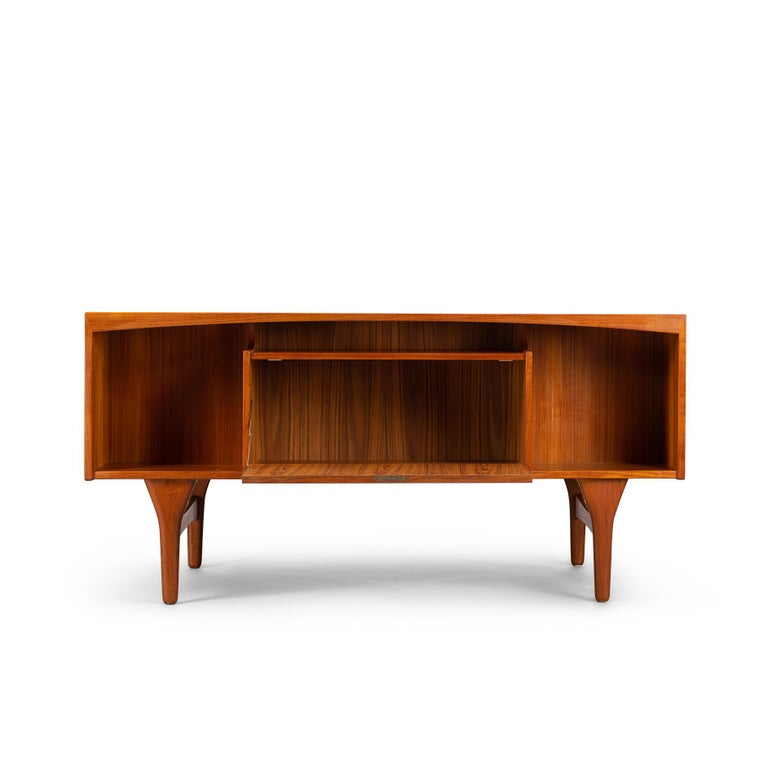 Fantastic freestanding sunburst teak desk designed and made by Valdemar Mortensen in the 1960s. It is a mid sized stylish midcentury desk in teak. Eclectic freestanding design with a semi floating top that is one with the drawer blocks through the