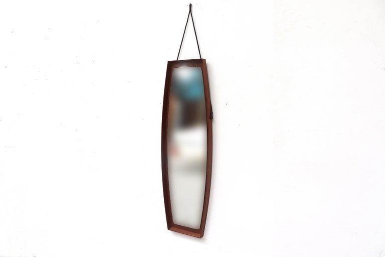 Midcentury wall mirror with teak frame and Leather strap. Mirror measures 47