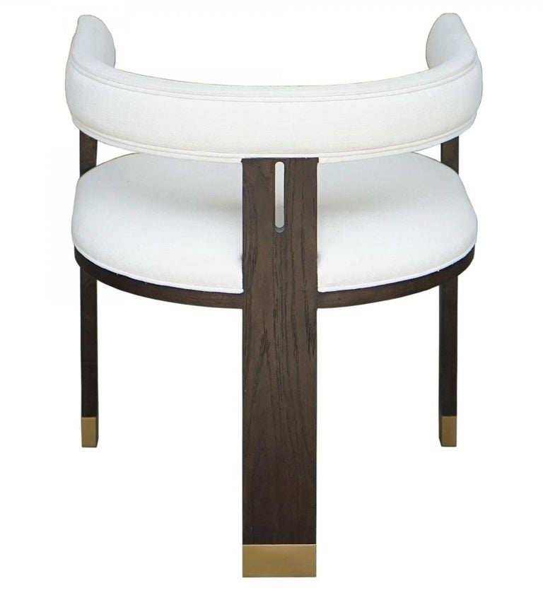 The chair features curved back and brass detailing. Handcrafted of solid oak frame and upholstered in white linen. Overall measures: 22