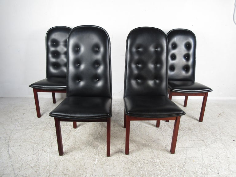 Nice Mid-Century Modern dining set. Danish modern dining chairs made by Domino Mobler, with rosewood frames and tufted black vinyl upholstery. Spacious table with two leaves; each leaf adds an additional 20 inches to the table's width. Please