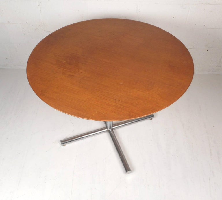 This unique vintage modern table functions as a kitchen table, a card table, or a dining table. Sleek design with gorgeous wood grain on the top and a heavy chrome base. This wonderful midcentury piece has one large cylindrical chrome support