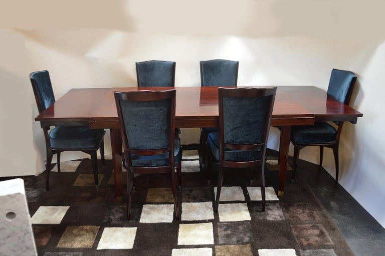 Mid-Century modern dining table. Legs of the mahogany table are capped and accented with brushed brass feet.