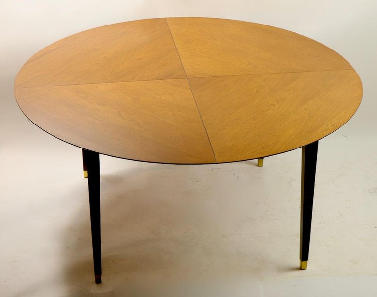 Architectural midcentury dining table having a round top with quartered line delineations and a beveled edge, on squared tapered legs with brass sabot feet Well constructed, nice usable scale, quality materials and sophisticated design. Clean, ready
