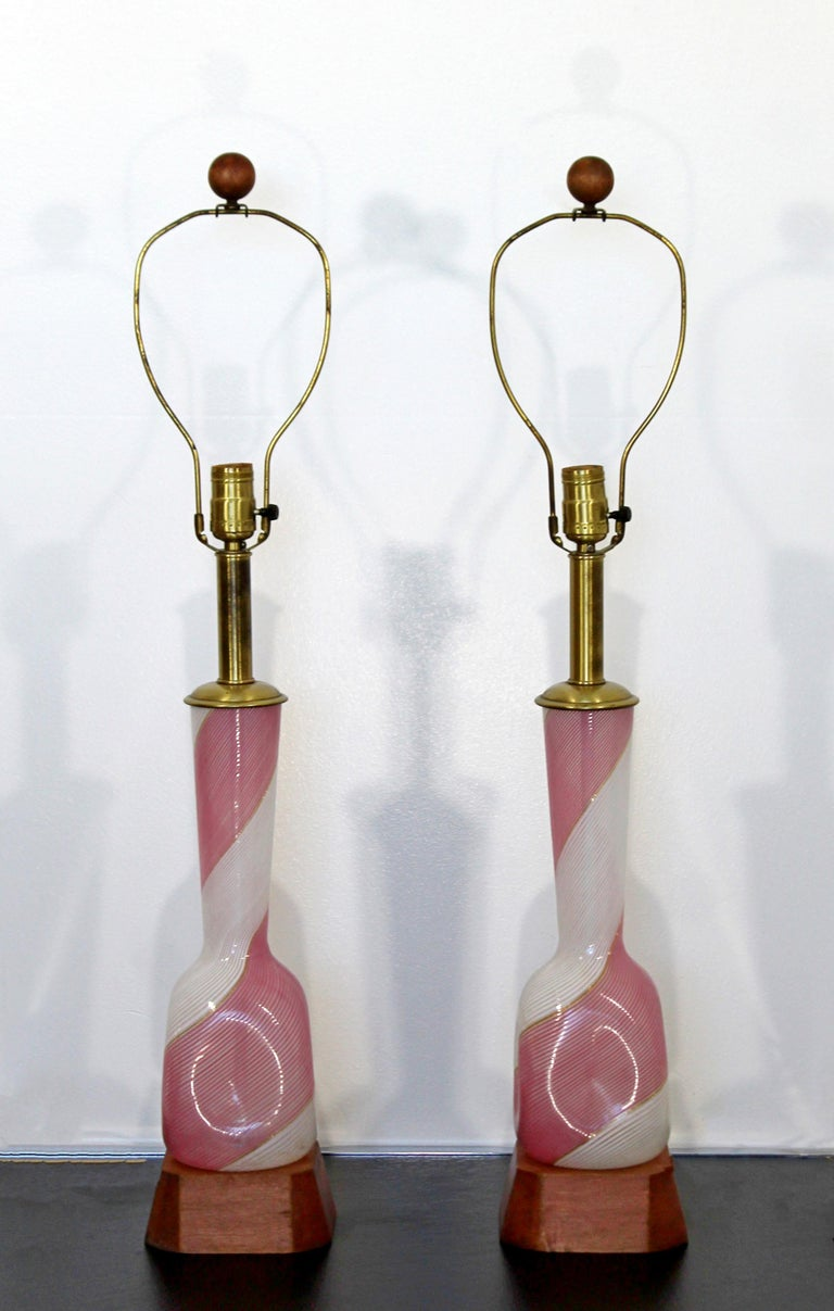 For your consideration is a gorgeous pair of pink Murano glass table lamps, with wood bases and original finials, by Dino Martens for Murano designed by Marbro, circa the 1970s. In excellent condition. The dimensions of each are 5.5