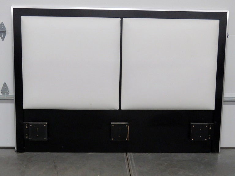 Mid-Century Modern ebonized headboard with leather upholstery and chrome trim.